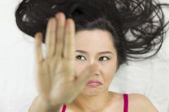 Closeup portrait of moody asian women  lying on ground with black long hair. acting upset , unhappy stock photo