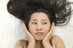 Closeup portrait of moody asian women  lying on ground with black long hair. acting upset , unhappy royalty free stock image