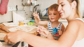Closeup portrait of young mother with toddler boy holding baking pan and making cookies on kitchen. Closeup portrait of mother with toddler boy holding baking stock photography