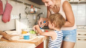 Closeup portrait of young mother with toddler boy holding baking pan and making cookies on kitchen. Closeup portrait of mother with toddler boy holding baking royalty free stock photo