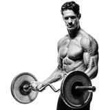 Closeup portrait of a muscular man workout with barbell at gym. Brutal bodybuilder athletic man with six pack, perfect abs, shoulders, biceps, triceps and Royalty Free Stock Photo