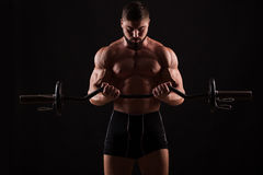 Closeup portrait of a muscular man workout with barbell at gym. stock photo