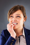 Closeup portrait of a nervous young businesswoman biting her fin. Gers against gray background Stock Images