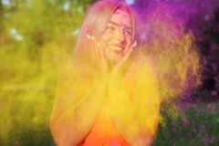 Closeup portrait of nice blonde woman having fun in a cloud of yellow and purple dry Holi paint stock images
