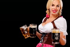 Closeup portrait of Oktober fest girl - waitress, wearing a traditional Bavarian dress, serving big beer mugs on black. Half-length portrait of young blonde with stock image