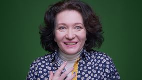 Closeup portrait of old caucasian brunette female being excited and surprised celebrating happily looking at camera with. Background isolated on green stock video