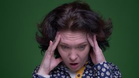 Closeup portrait of old caucasian brunette female having a headache and being tired in front of the camera with. Background isolated on green stock video footage