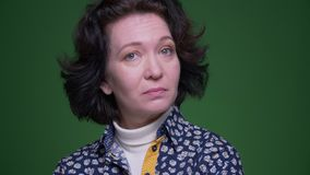 Closeup portrait of old caucasian brunette female nodding sating yes looking at camera with background isolated on green stock footage