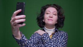 Closeup portrait of old caucasian brunette female taking selfies on the phone with background isolated on green stock footage