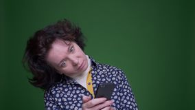 Closeup portrait of old caucasian brunette female using the phone with background isolated on green stock video footage