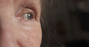 Closeup portrait of old womans eyes stock photography