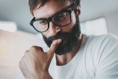 Closeup portrait of pensive bearded designer wearing eye glasses and working at the modern lightful office loft Stock Photo
