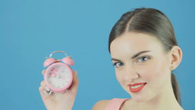 Closeup Portrait of Perfect Cute Brunette with Pink Clock in Hand and Charming Smile on Blue Background in Studio. Time