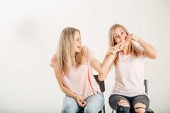 Closeup portrait picture of woman biting finger of her sister. Closeup portrait picture of women biting finger of her sister stock image