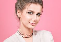 Closeup portrait of in pink. Beautiful young woman in a light blouse. On a pink background. Beads or decoration on the neck. Hairstyle and professional makeup royalty free stock photos