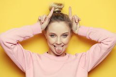 Portrait of playful young pretty blond woman showing horns and making faces. Isolated on yellow background. Closeup portrait of playful young pretty blond woman stock photos