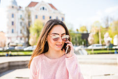 Closeup portrait of positive brunette girl speaking on phone on sunny street . Royalty Free Stock Image