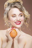 Closeup Portrait of Positive Caucasian Blond Girl with One Orange Stock Photography