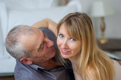 Closeup Portrait of Pretty Beautiful Young Woman in Sexy Lingerie Hugging Her Senior Husband Lying in Bed. Couple with. Age Difference Stock Photo