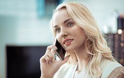 Closeup portrait of a pretty blonde using a smartphone Stock Photography