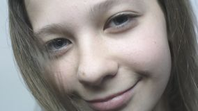 Close-up portrait of a young girl looking in the camera and smiling in slowmo. stock footage
