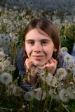 Closeup Portrait of Pretty Girl Resting on Dandelion Field on Sunny Spring Day. Closeup Portrait of Pretty Girl With Freckles Sprinkled Across Her Nose Leaning Royalty Free Stock Images