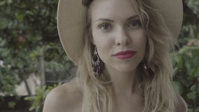 Closeup portrait of pretty naturally looking woman on summer day wearing hat and earrings smiling and looking into the camera. stock video footage