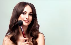Closeup portrait of pretty woman with cosmetics brush stock images