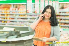 Closeup portrait of pretty young caucasian woman brunette talking on the phone and choosing goods in supermarket store.  Royalty Free Stock Images