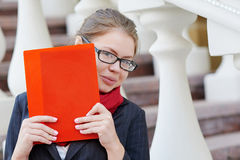 Closeup portrait of pretty young student girl holding exercise books and folder Stock Images