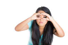 Closeup portrait of pretty young woman looking for something with squinting eyes and imaginary binocular Stock Photo