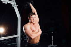 Closeup portrait of professional bodybuilder Strong muscular yang man doing exercise. Workout with barbell at gym Royalty Free Stock Images