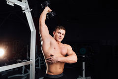 Closeup portrait of professional bodybuilder Strong muscular yang man doing exercise. Workout with barbell at gym Royalty Free Stock Image