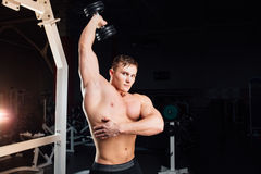 Closeup portrait of professional bodybuilder Strong muscular yang man doing exercise. Workout with barbell at gym Stock Photo