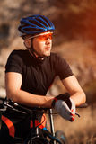 Closeup portrait of professional cyclist with his bicycle in the countryside Royalty Free Stock Photography