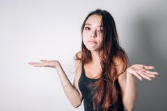 Closeup portrait puzzled clueless young woman with arms out asking what is problem who cares so what I don`t know stock photo