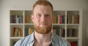 Closeup portrait of redhead bearded caucasian male student smiling happily looking at camera in the library.  stock video