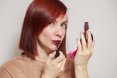 Closeup portrait redhead beautiful girl looking in mirror compact powder and paints lips with dark burgundy purple liquid lipstick stock photography