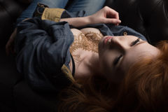 Closeup portrait of a redhead girl in a denim shirt and a black bra with a mehendi on her chest lying on the couch. Horizontal photo Stock Photos