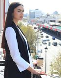 Closeup portrait of relaxing on balcony business woman  on background of city buildings. Royalty Free Stock Image