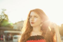 Closeup portrait of romantic redhead girl with freckles wearing. Closeup portrait of romantic redhead woman with freckles wearing glasses, posing in evening soft royalty free stock images
