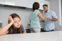 Closeup portrait of a sad girl while parents quarreling. In the kitchen Stock Photography