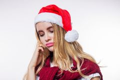Closeup portrait of sad upset beautiful blonde woman wearing red Santa hat on white background. Bad mood, disappointment in the stock photography
