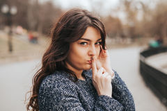 Closeup portrait secretive young woman placing finger on lips. Asking shh, quiet, silence looking. Human face expressions, sign emotion royalty free stock photo