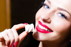 Closeup portrait on seductive charming beautiful young woman with blue eyes, red lips & hand with red nails holding candy Royalty Free Stock Image