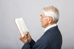 Closeup portrait of senior man with glasses standing and reading Royalty Free Stock Images