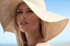 Closeup portrait of a sensual blonde wearing a straw hat royalty free stock photography