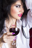 Closeup portrait of sensual brunette young woman in man's shirt. Holding a glass of wine in the bedroom Royalty Free Stock Image