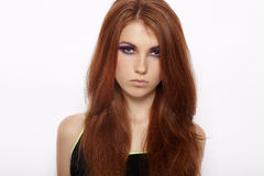 Closeup portrait of serious cute redhead woman with violet smokey eyes makeup looking into camera isolated. Closeup portrait of serious cute redhead lady with Royalty Free Stock Images