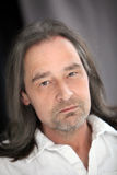 Serious unshaven man with long hair Stock Photo